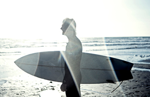 Side view of man in wetsuit standing by the ocean, carrying surfboard.の写真素材 [FYI02258992]
