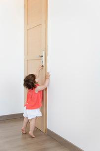 Baby girl in red top trying to open closed wooden door.の写真素材 [FYI02259001]