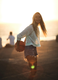 Young woman standing in front of a sunset holding a basketball.の写真素材 [FYI02259017]