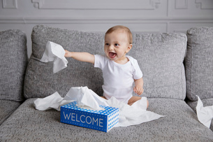 Baby boy with blond hair sitting on sofa, playing with tissue paper.の写真素材 [FYI02259028]