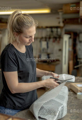 Blond woman standing in a workshop, cutting bubble wrap with pair of scissors, wrapping a parcel forの写真素材 [FYI02259062]