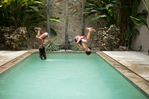 Two children in mid air, somersaulting backwards into a swimming pool.の写真素材 [FYI02259076]