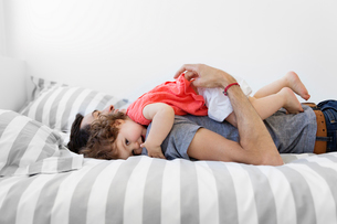 Man wearing grey T-shirt and jeans lying on bed with stripy duvet, hugging baby girl in red dress.の写真素材 [FYI02259078]