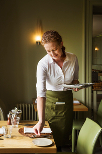 Woman wearing apron setting table in a restaurant.の写真素材 [FYI02259080]