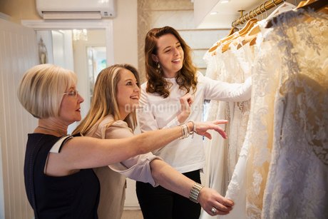 Three women in a wedding dress boutique looking at a rail of white bridal gowns, with lace and decorの写真素材 [FYI02259092]