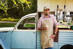 Bearded man wearing apron standing by blue mobile coffee shop, holding hot drink, smiling at camera.の写真素材 [FYI02259095]