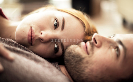 A couple lying together on the floor.の写真素材 [FYI02259108]