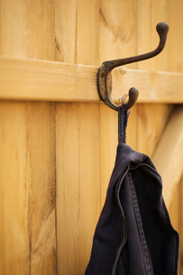 A black jacket hanging from a metal coathook on the back of a wooden door.の写真素材 [FYI02259128]