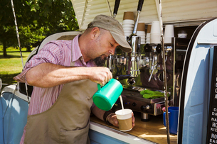 Bearded man wearing apron standing by blue mobile coffee shop, making coffee.の写真素材 [FYI02259145]
