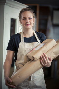 A young woman in a workshop, holding two packages wrapped in brown packaging paper, ready for despatの写真素材 [FYI02259149]