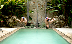 Two children in mid air, somersaulting backwards into a swimming pool.の写真素材 [FYI02259152]