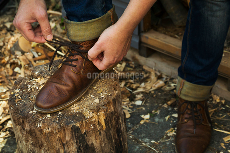 A man in denim jeans with turnups sitting leaning down to tie his shoe laces of his brown leather shの写真素材 [FYI02259155]