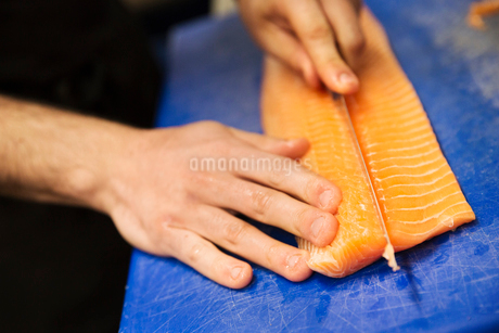 Close up high angle view of person, cutting a fillet of salmon on a blue chopping board.の写真素材 [FYI02259158]