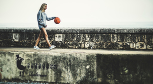 Young woman walking on a wall bouncing a basketball.の写真素材 [FYI02259165]
