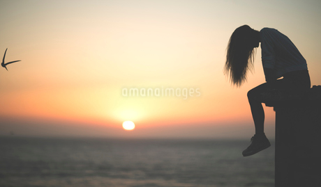 Side view of a young woman sitting on a wall with a sunset behind.の写真素材 [FYI02259166]