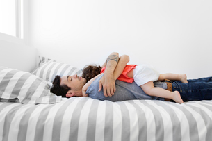 Man wearing grey T-shirt and jeans lying on bed with stripy duvet, hugging baby girl in red dress.の写真素材 [FYI02259180]