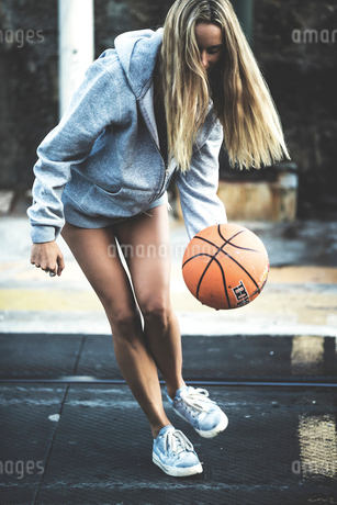 Young woman standing and bouncing a basketball.の写真素材 [FYI02259190]