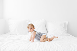 Baby boy wearing striped onesie lying on bed with white duvet.の写真素材 [FYI02259194]