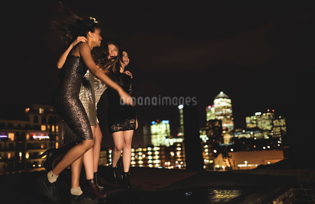 Group of young women standing on a rooftop celebrating.の写真素材 [FYI02259206]