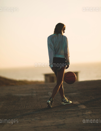 Young woman standing in front of a sunset.の写真素材 [FYI02259210]