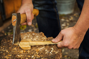 Close up of person holding a hand axe, cutting and shaping a small piece of wood on a splitting blocの写真素材 [FYI02259212]