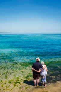 Rear view of elderly couple standing with arms around shoulders looking out to sea across the vividの写真素材 [FYI02259223]
