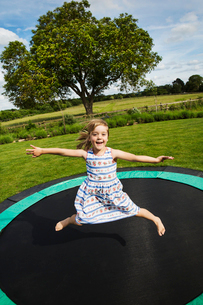Girl in a sundress jumping on a trampoline in a garden.の写真素材 [FYI02259231]