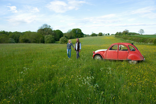 Man and woman walking hand in hand across a meadow, vintage red car parked close by.の写真素材 [FYI02259234]