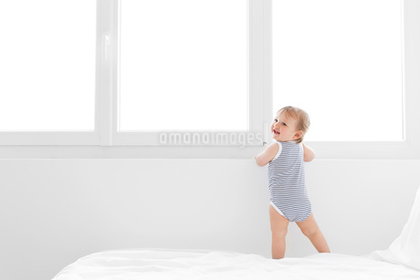 Baby boy wearing striped onesie standing on bed with white duvet.の写真素材 [FYI02259259]