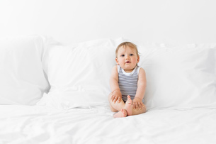 Baby boy wearing stripy onesie sitting on a bed with white duvet, hand on knees.の写真素材 [FYI02259262]