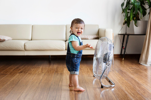 Young boy wearing denim dungarees, standing on hardwood floor in front of electric fan.の写真素材 [FYI02259263]