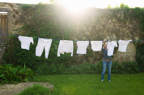 Woman standing on a lawn in a garden, hanging up laundry on washing line.の写真素材 [FYI02259266]