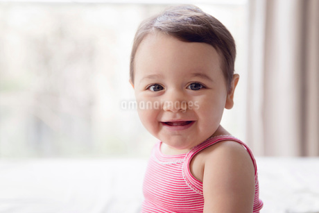 Smiling baby girl with brown hair wearing pink onesie, sitting on a bed, looking at camera.の写真素材 [FYI02259267]