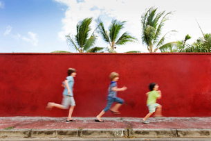 Three children, boys in age and height order, running along by a red wall.の写真素材 [FYI02259276]