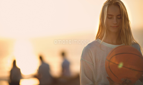 Young woman standing in front of a sunset holding a basketball.の写真素材 [FYI02259284]