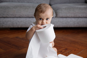 Baby boy with blond hair sitting on hardwood floor, playing with toilet paper rolls.の写真素材 [FYI02259286]