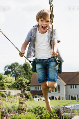 Smiling boy wearing shirt and denim shorts on a swing in a garden.の写真素材 [FYI02259299]