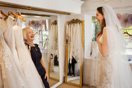 A woman, a bride to be, trying on dresses with the help of a sales assistant, in a wedding dress shoの写真素材 [FYI02259302]