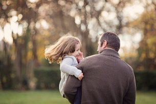 Man standing outdoors, holding smiling young girl with brown hair.の写真素材 [FYI02259319]