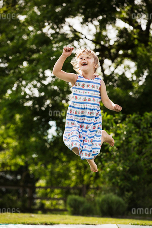 Girl in a sundress jumping on a trampoline in a garden.の写真素材 [FYI02259331]