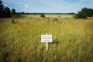 White 'Keep Off' sign on a meadow with river and trees in the distance.の写真素材 [FYI02259334]