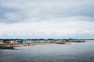 Long row of painted beach huts on a sandy beach overlooking the water.の写真素材 [FYI02259338]