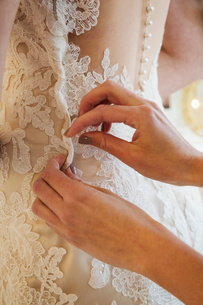 A dressmaker taking in a wedding dress, pinning and fitting it to the client.の写真素材 [FYI02259342]