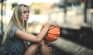 Young woman sitting on a railway station platform holding a basketball with a train behind.の写真素材 [FYI02259349]