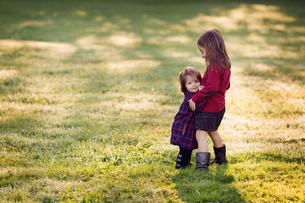 Young girl wearing checkered dress, standing outdoors on lawn, hugging girl.の写真素材 [FYI02259361]