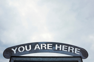 Low angle close up of 'You are Here' sign under a cloudy sky.の写真素材 [FYI02259365]