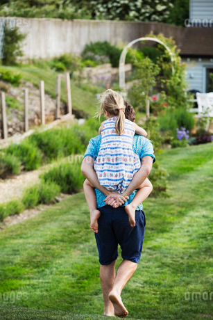 Rear view of a man walking across a lawn, carrying a girl on his back.の写真素材 [FYI02259373]