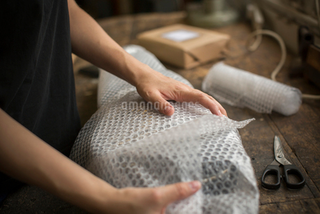 A woman wrapping an item in bubble wrap, a parcel being prepared for despatch.の写真素材 [FYI02259378]