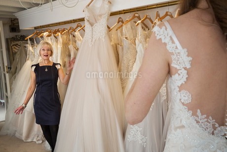A woman, a bride to be, trying on dresses with the help of a sales assistant, in a wedding dress shoの写真素材 [FYI02259388]
