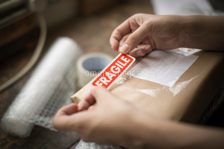 Hands holding a red Fragile sticker to stick it on a brown paper package on a work bench.の写真素材 [FYI02259391]